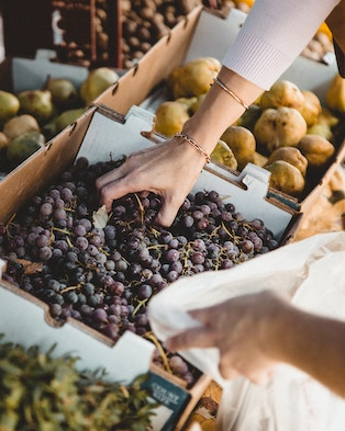 Woman picking purple grapes at a farmers' market